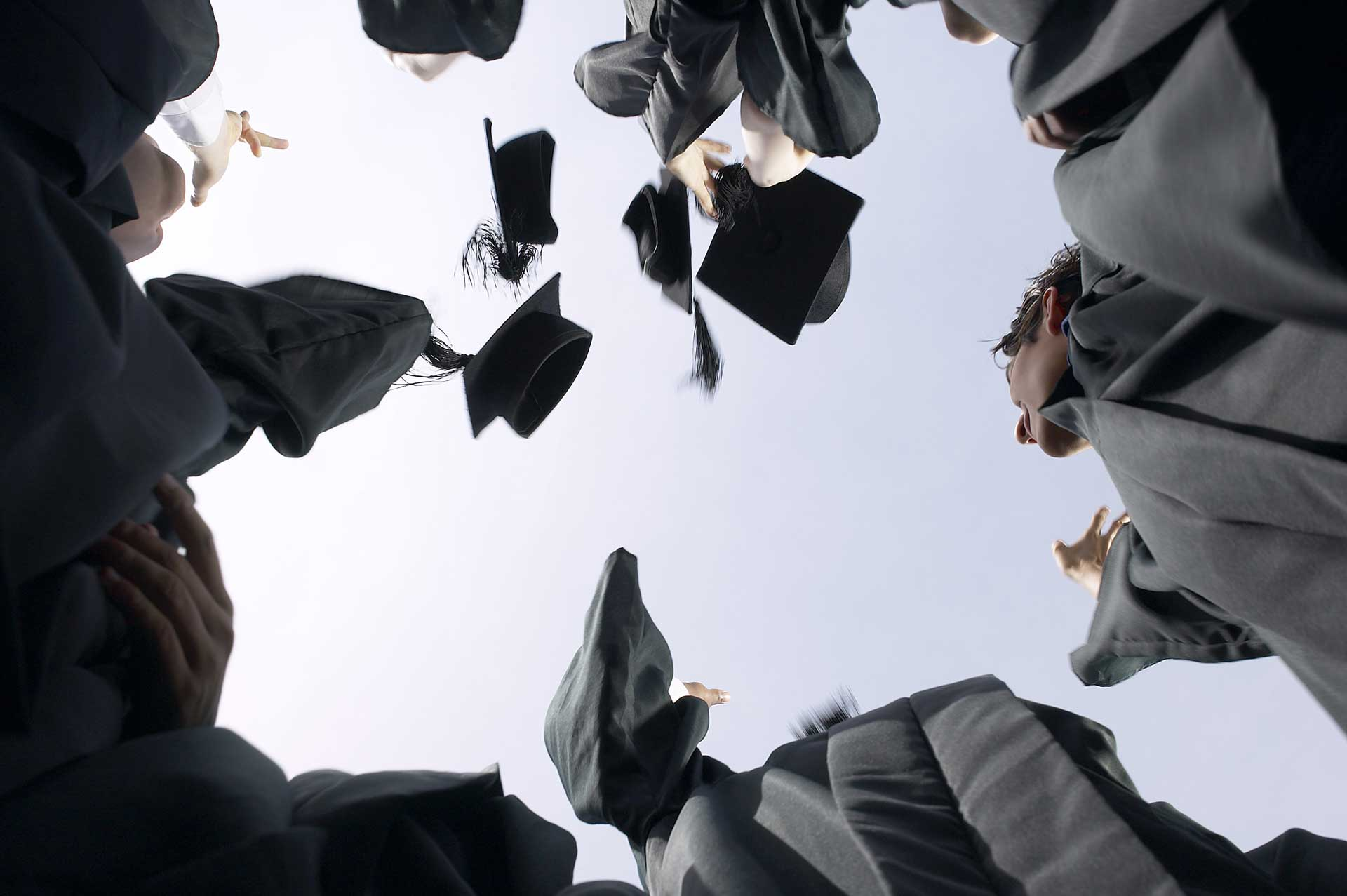 students in black graduation gowns throwing their caps into the sky