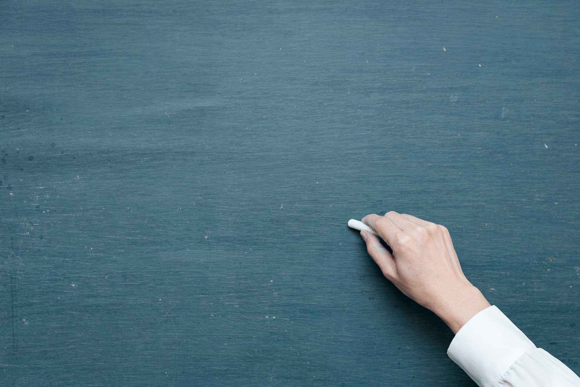Hand about to write on clean chalkboard