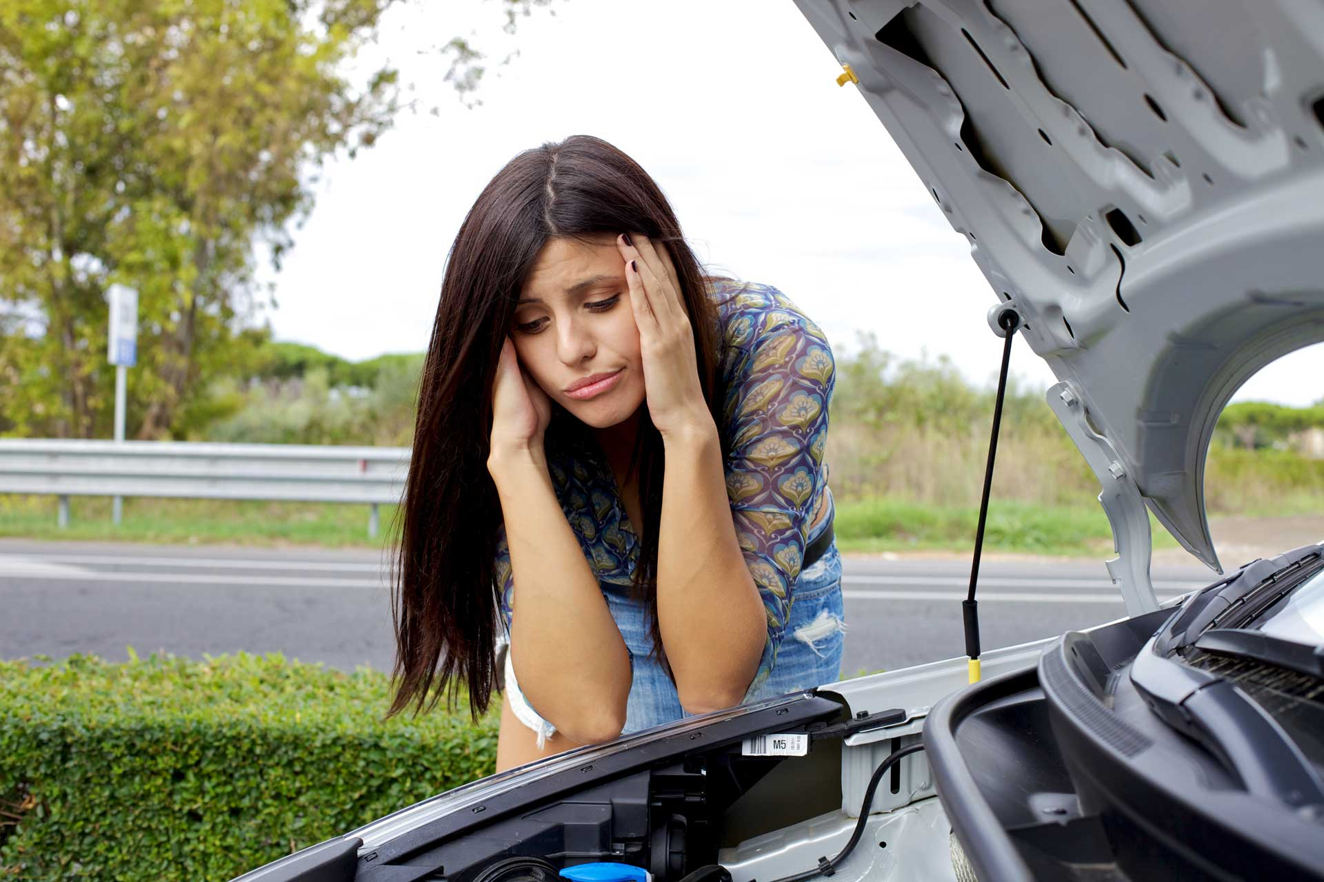 Sad girl leaning over open car hood to look at broken engine