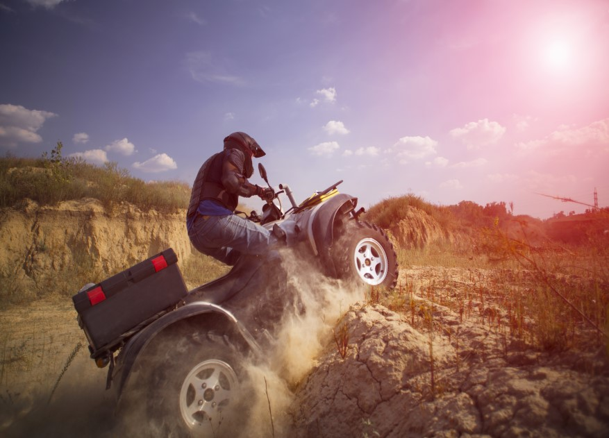 Man in safety gear riding ATV over dirt pile