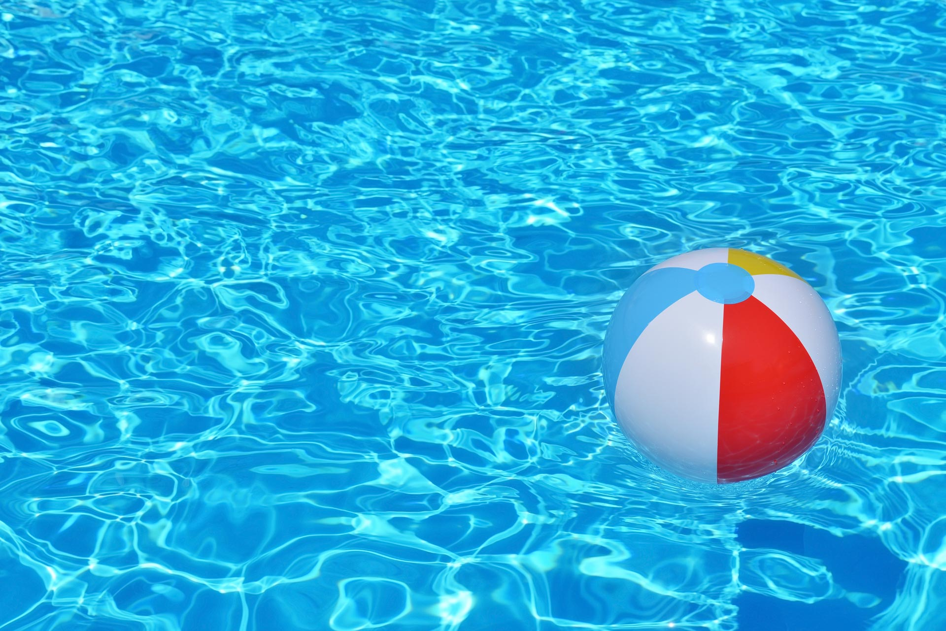 Red, white, yellow and blue beach ball floating in crystal clear blue water
