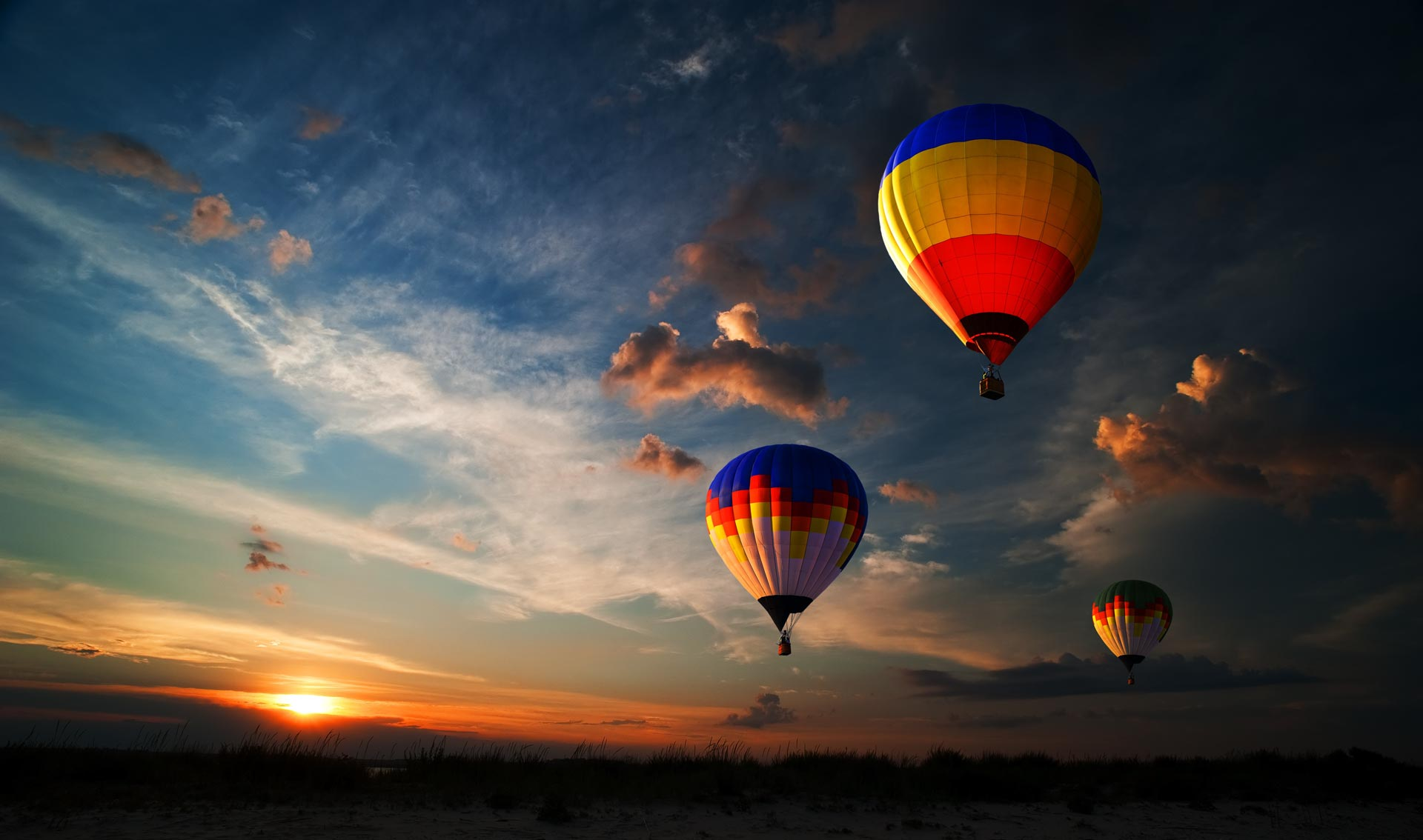 Three hot air balloons ascending into a dark sky with a sunset in the background