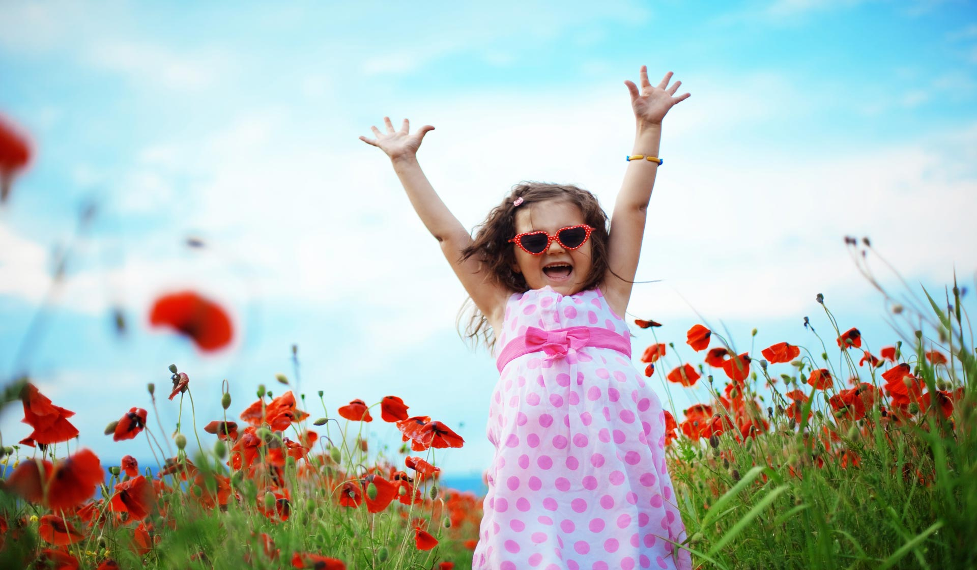 Little girl running in red flower field with her hands up in the air