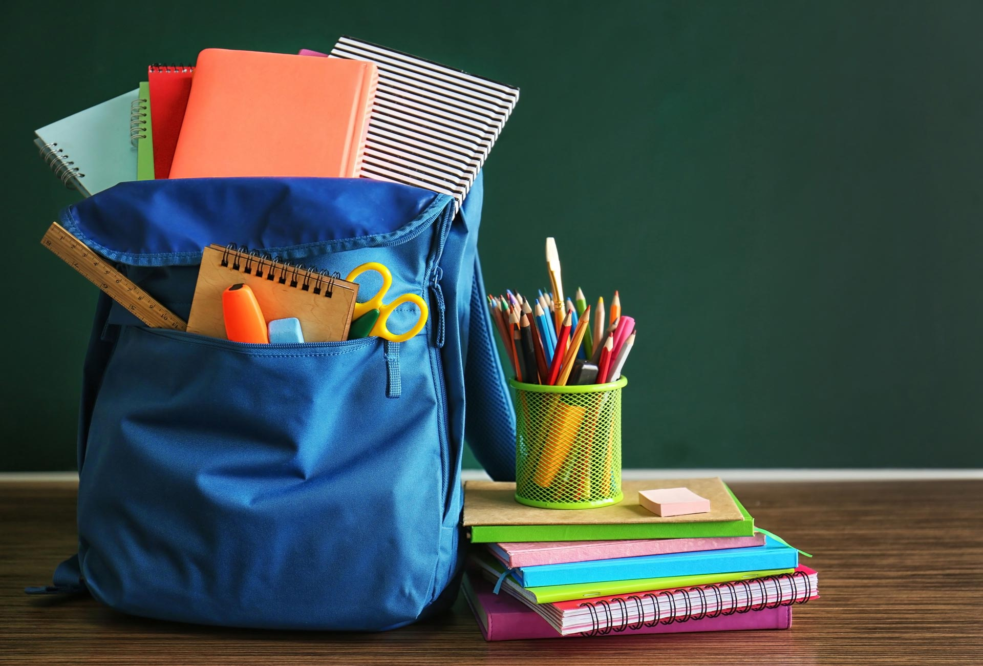 Blue backpack with school supplies stuffed in it