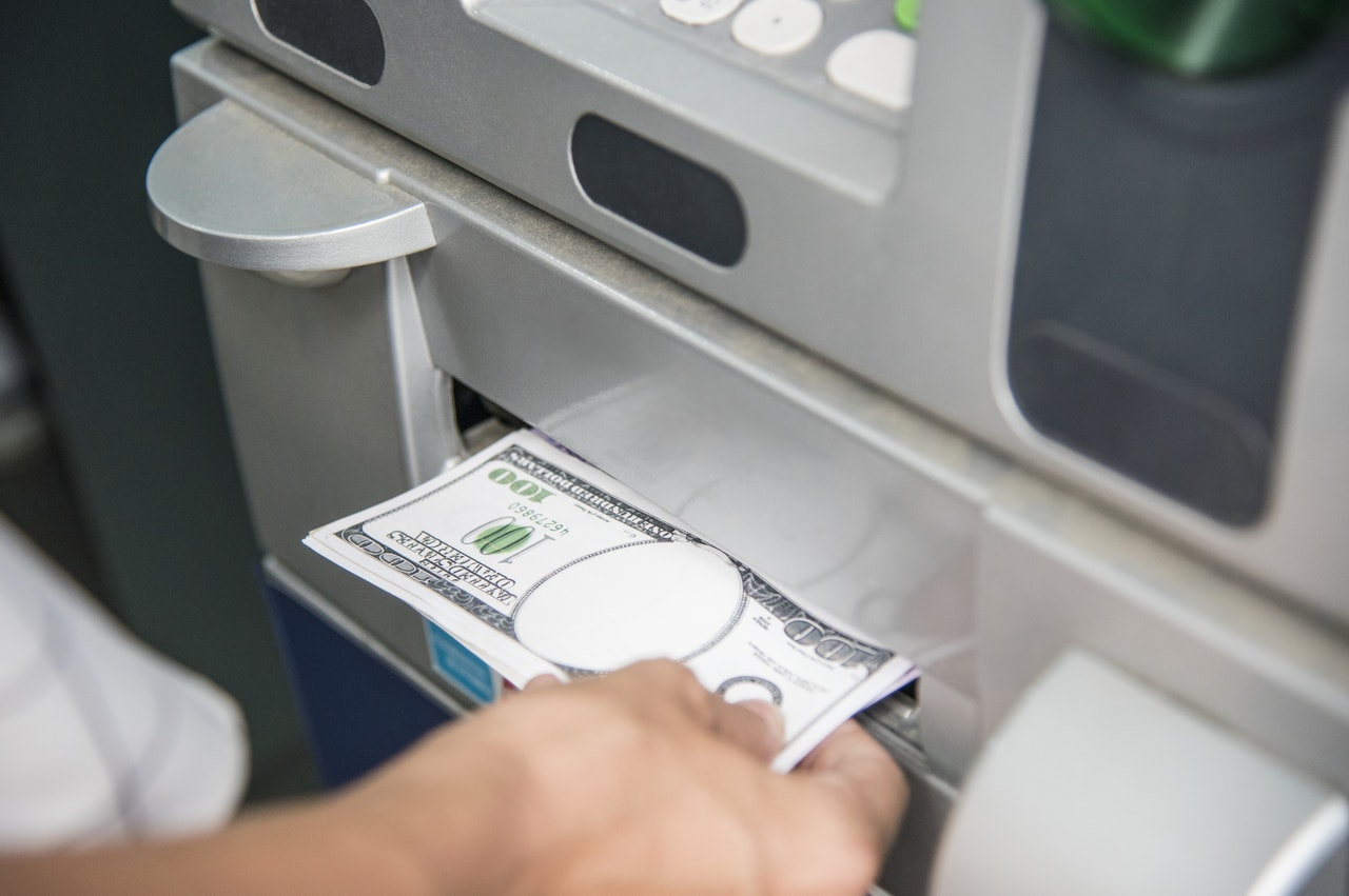 Hand pulling money out of ATM dispenser